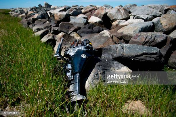 An abandoned outboard boat motor sits against the manmade sea wall that was engineered by the Army Corps of Engineers in 1999 to prevent erosion in...