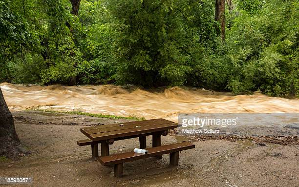 CONTENT] An abandoned water bottle sit at a picnic table next to the raging waters of Boulder Creek during the 2013 Colorado flood