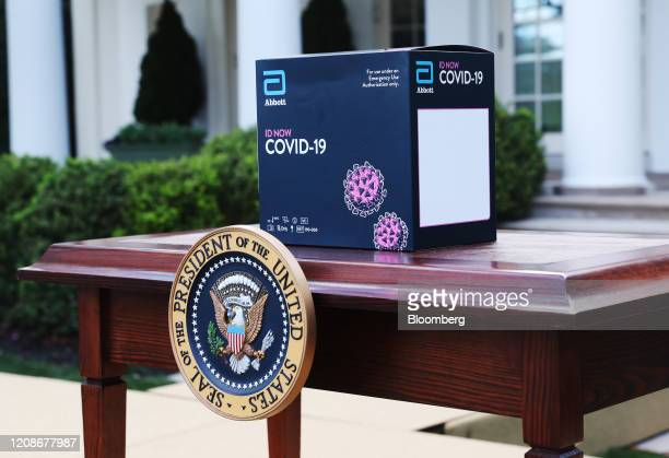 An Abbott Laboratories ID Now Covid-19 test kit box sits on a table before a Coronavirus Task Force news conference in the Rose Garden of the White...