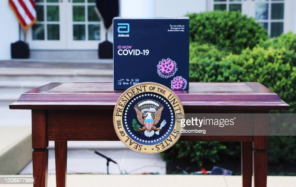 An Abbott Laboratories ID Now Covid19 test kit box sits on a table before a Coronavirus Task Force news conference in the Rose Garden of the White...