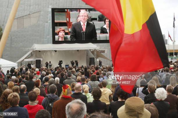 An Aboriginal flag waves in front of the giant television screen as thousands gather in Melbourne's Federation Square on February 13 2008 to listen...