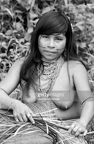 An aboriginal girl with bare breast is plaiting straw outdoor Latin America 1970