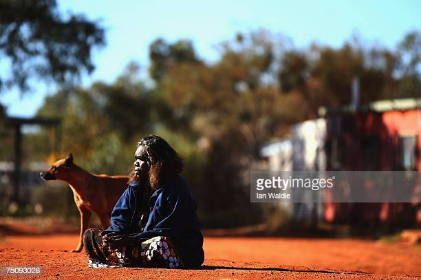 An Aboriginal woman sits on the ground as Indigenous Affairs Minister Mal Brough arrives for a meeting with the Mutitjulu community July 6 2007 in...