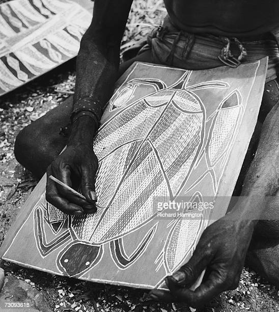 An Aborigine draws a picture of a turtle on a piece of flattened bark circa 1955