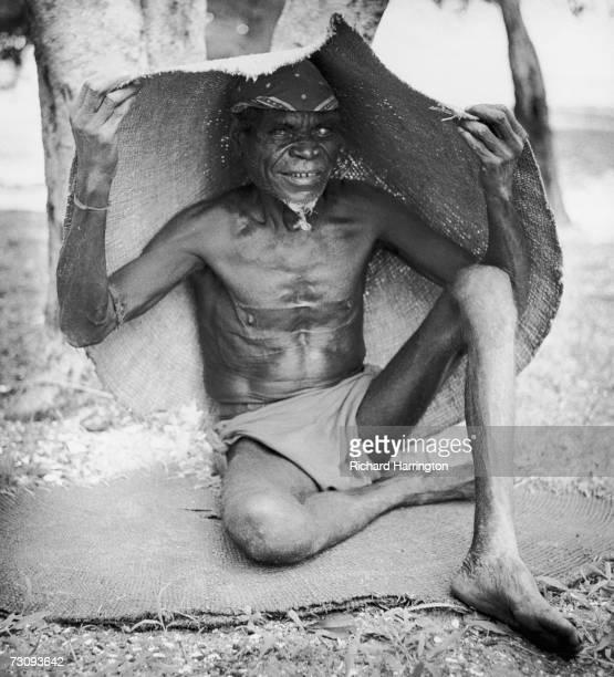 An Aborigine shelters under a woven mat circa 1955