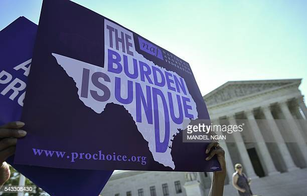 An abortion rights activist holds placards outside of the US Supreme Court before the Court struck down a Texas law placing restrictions on abortion...