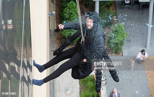 An abseiling spider sprays its web as its descends the outside wall at the Australian Museum on October 28 2016 in Sydney Australia The event was to...