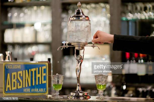 An absinthe fountain seen on the counter at the bar of the 'Casablanca' cinema in Nuremberg Germany 19 May 2016 Perforated metal spoons with hooks...