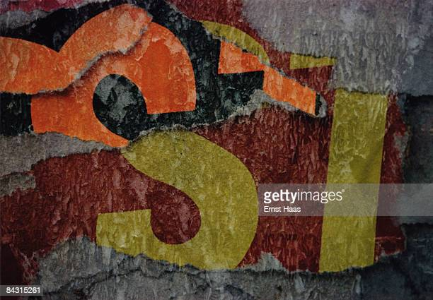 An abstract closeup of fragmented lettering in layers of torn posters USA circa 1970
