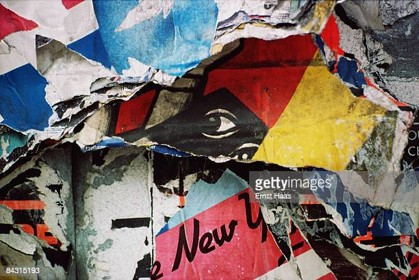 An abstract closeup of patterns formed by layers of torn posters with a depiction of a human eye at the centre USA circa 1970