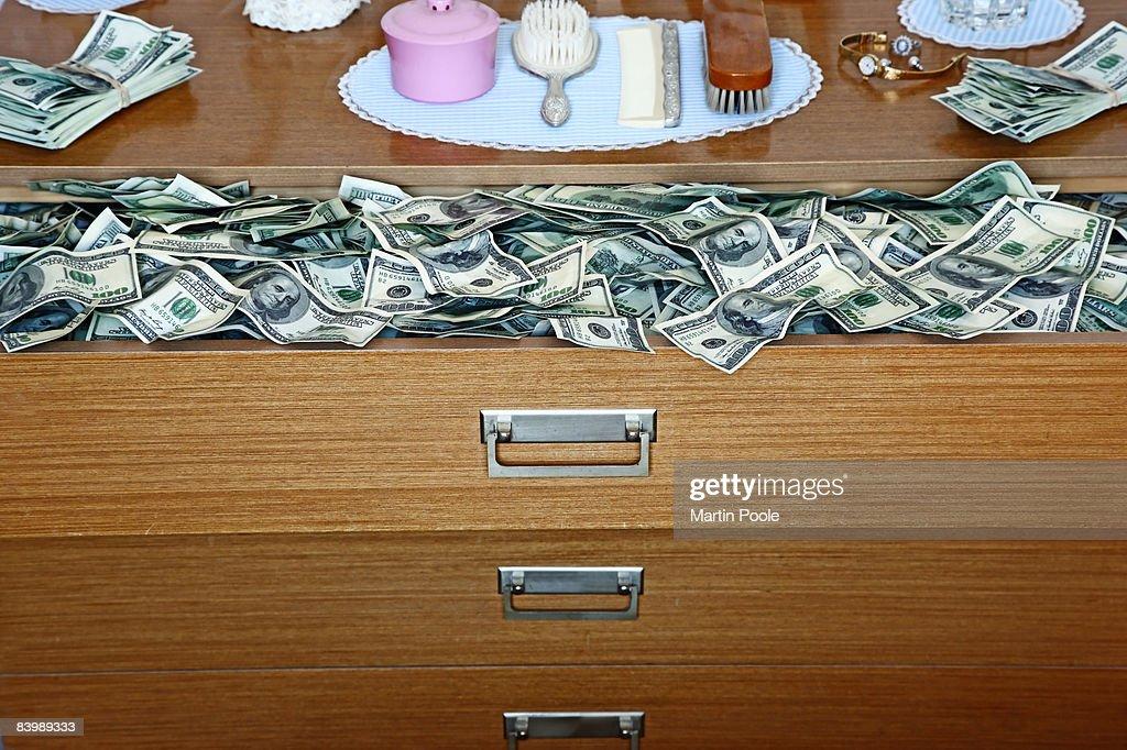 an abundance of 100 dollar bills in old dresser : Stock Photo