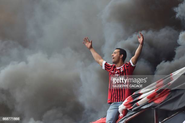 An AC Milan's supporter cheers before the Italian Serie A football match Inter Milan vs AC Milan at the San Siro stadium in Milan on April 15 2017 /...