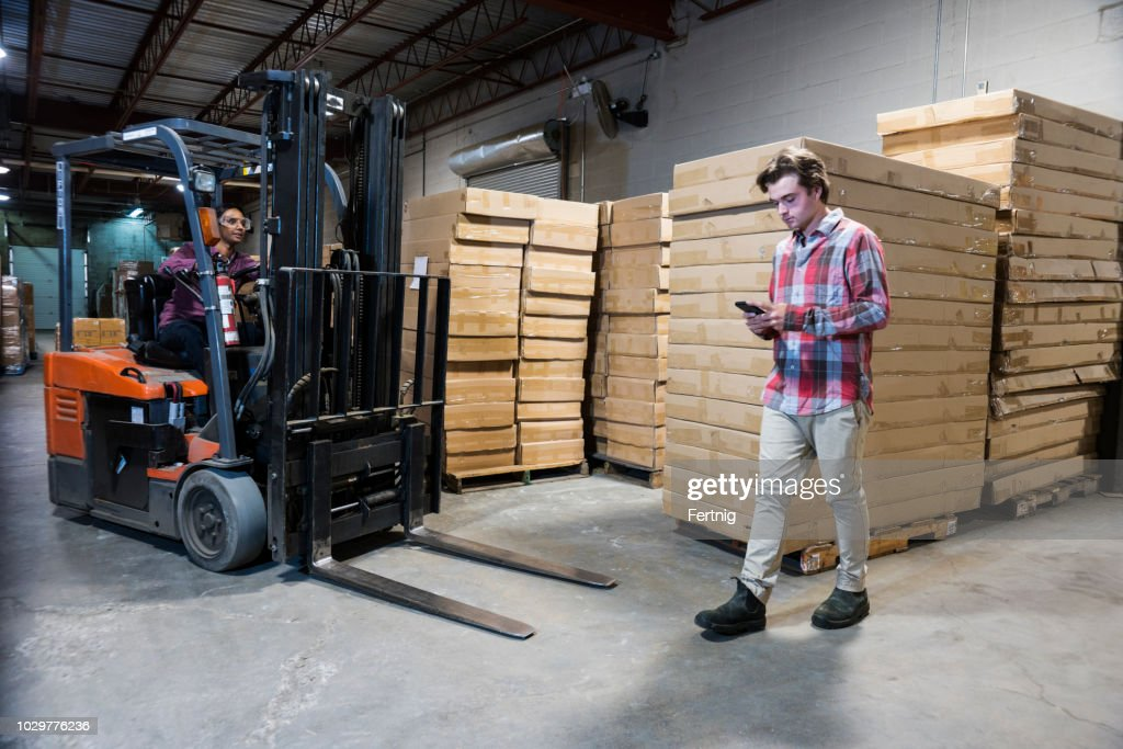 An accident waiting to happen.  An industrial worker using a cell phone in a warehouse. : Stock Photo