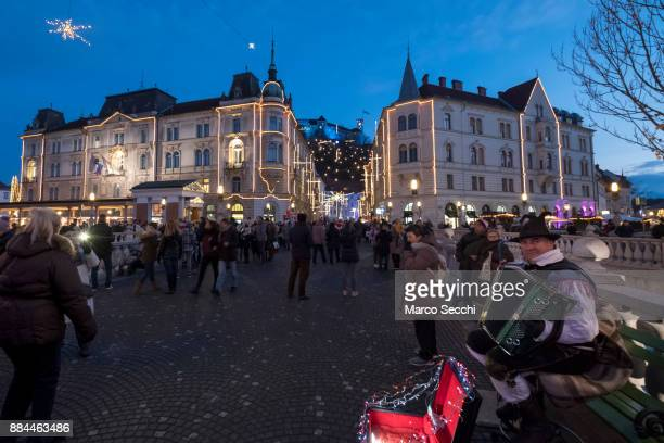 An accordian player entertains passers by on Triple Bridge on December 2 2017 in Ljubljana Slovenia The traditional Christmas market and lights will...