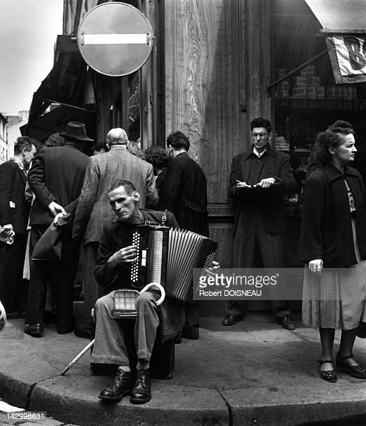 An Accordionist is playing in the street rue Mouffetard 1951 in Paris France