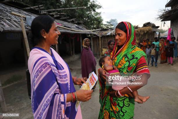 An Accredited Social Health Activist interacts with a young mother during a home visit ASHAs are trained and supported by Pathfinder International to...