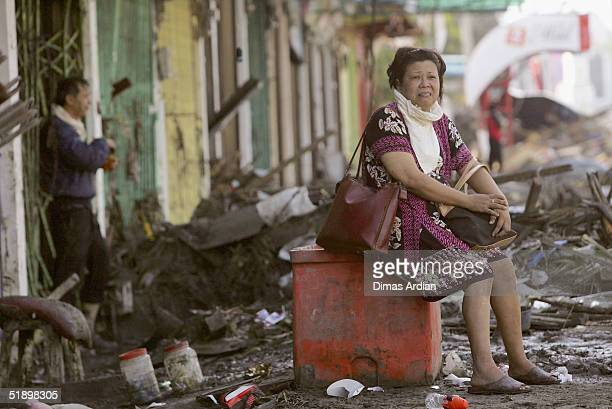 An Aceh resident sits in a street after a Tsunami hit the 150 miles from southern Asia's massive earthquake's epicenter on December 28 2004 in Banda...