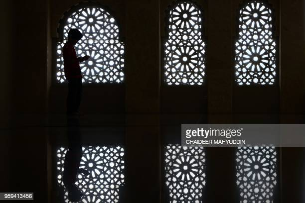 TOPSHOT An Acehnese boy recites the Koran at a mosque on the first day of the Muslim holy fasting month of Ramadan in Banda Aceh on May 17 2018...