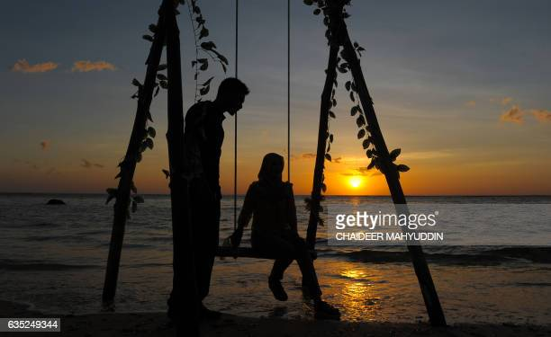 TOPSHOT An Acehnese couple enjoy the sunset at Lhok Nga beach during Valentine's day in Aceh on February 14 2017 / AFP PHOTO / CHAIDEER MAHYUDDIN