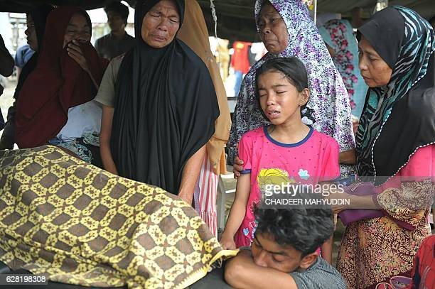 TOPSHOT An Acehnese family grieves for their relative who died after a powerful earthquake in Pidie Jaya Aceh province on December 7 2016 At least 52...