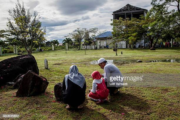 An Acehnese family prays at mass grave to commemorate the tenth anniversary of the Boxing Day tsunami on December 26 2014 in Banda Aceh Indonesia...