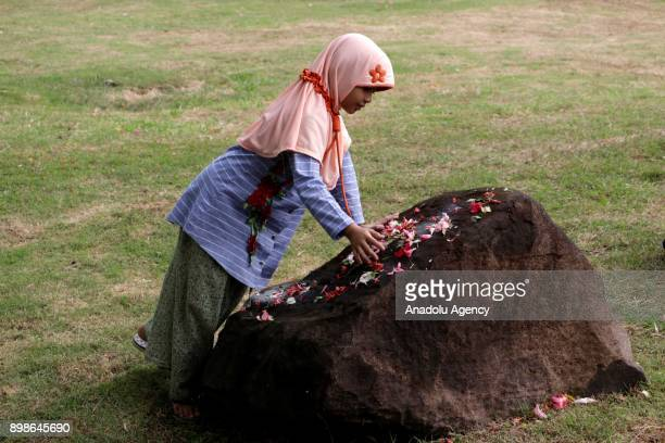 An Acehnese girl places flower leaves on a grave during the 13th anniversary of Tsunami commemoration at Ulee Lheue Banda Aceh in Aceh Indonesia on...