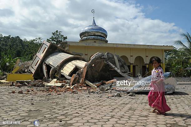 TOPSHOT An Acehnese girl walks past a collapsed mosque minater following an earthquake in Pidie Aceh province on December 7 2016 At least 25 people...