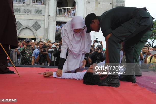 An Acehnese man collapses as he was getting caned by a religious officer for spending time in close proximity with a woman who is not his wife which...