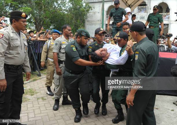 An Acehnese man gets carried away after he collapsed while getting caned by a religious officer for spending time in close proximity with a woman who...