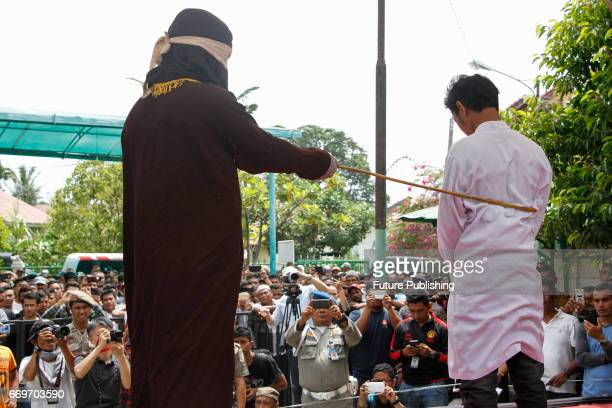An Acehnese man is being whipped in public for violating sharia law on April 18 2017 in Banda Aceh Indonesia About four Acehnese couple received 23...