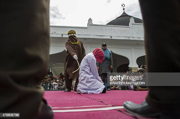 An Acehnese woman convicted for immoral acts is lashed by a hooded local government officer during a public caning at a square in Banda Aceh Aceh...
