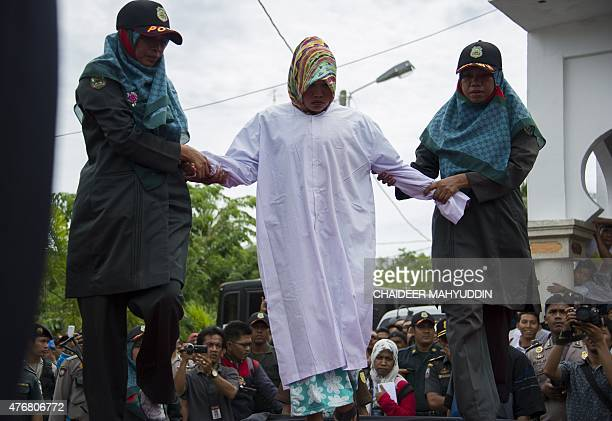 An Acehnese woman convicted for immoral acts prepares for her punishment to be administered by a hooded local government officer during a public...