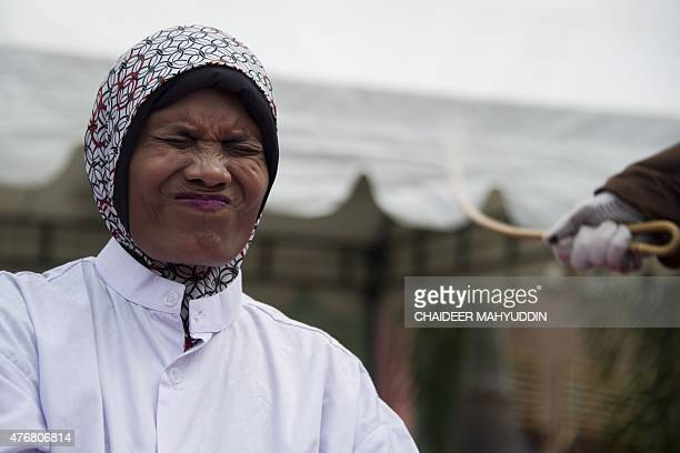 An Acehnese woman convicted for pimping reacts while lashed by a hooded local government officer during a public caning at a square in Banda Aceh...