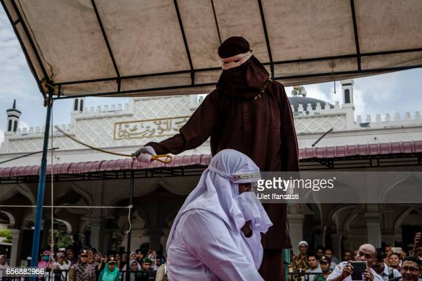 An acehnese woman gets caning in public from an executor known as 'algojo' for spending time with a man who is not her husband which is violations...