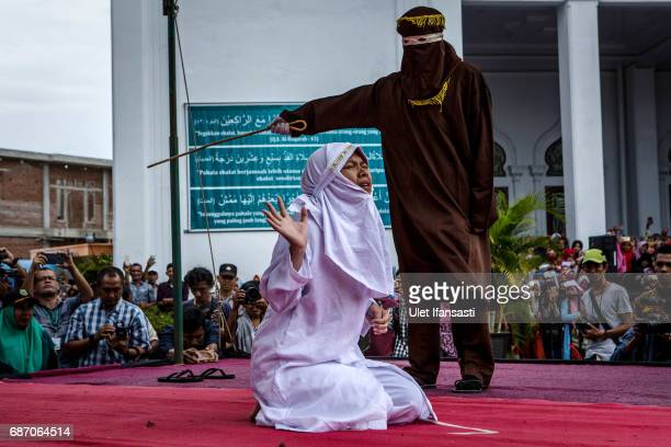 An acehnese woman gets caning in public from an executor known as 'algojo' for spending time with a man who is not her husband, which is against...