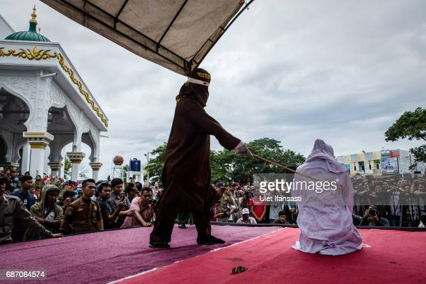 An acehnese woman gets caning in public from an executor known as 'algojo' for spending time with a man who is not her husband which is against...