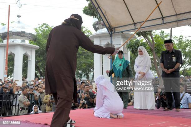 An Acehnese woman gets whipped for spending time in close proximity with a man who is not her husband which is against Sharia law in Aceh on March 20...