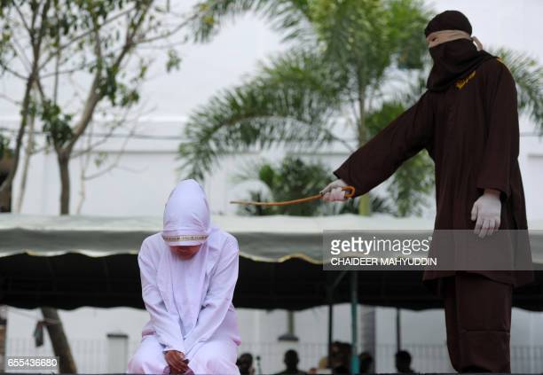 TOPSHOT An Acehnese woman gets whipped for spending time in close proximity with a man who is not her husband which is against Sharia law in Aceh on...