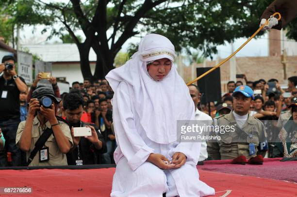 An Acehnese woman is being whipped in public for violating sharia law on May 23 2017 in Banda Aceh Indonesia About four Acehnese couple received 25...