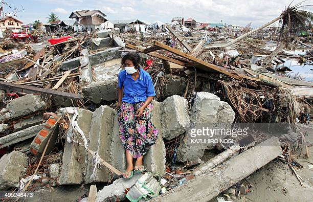 An Acehnese woman lingers at the ruins of her home in downtown Banda Aceh 11 Janaury 2005 The death toll from the earthquake and tsunami in Indonesia...