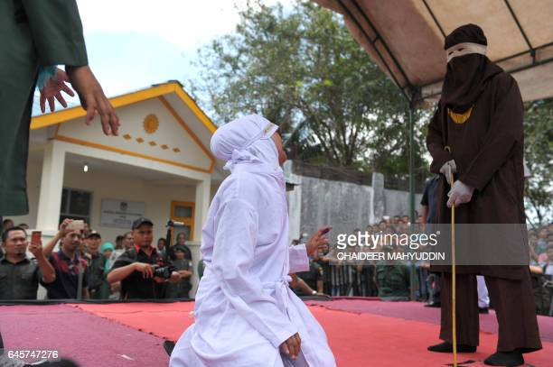 An Acehnese woman pleas to a religious officer who will cane her for spending time in close proximity with a man who is not her husband which is...