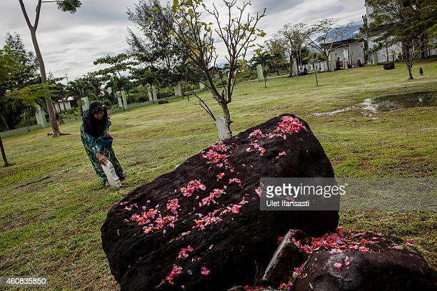 An Acehnese woman prays at mass grave to commemorate the tenth anniversary of the Boxing Day tsunami on December 26 2014 in Banda Aceh Indonesia Aceh...