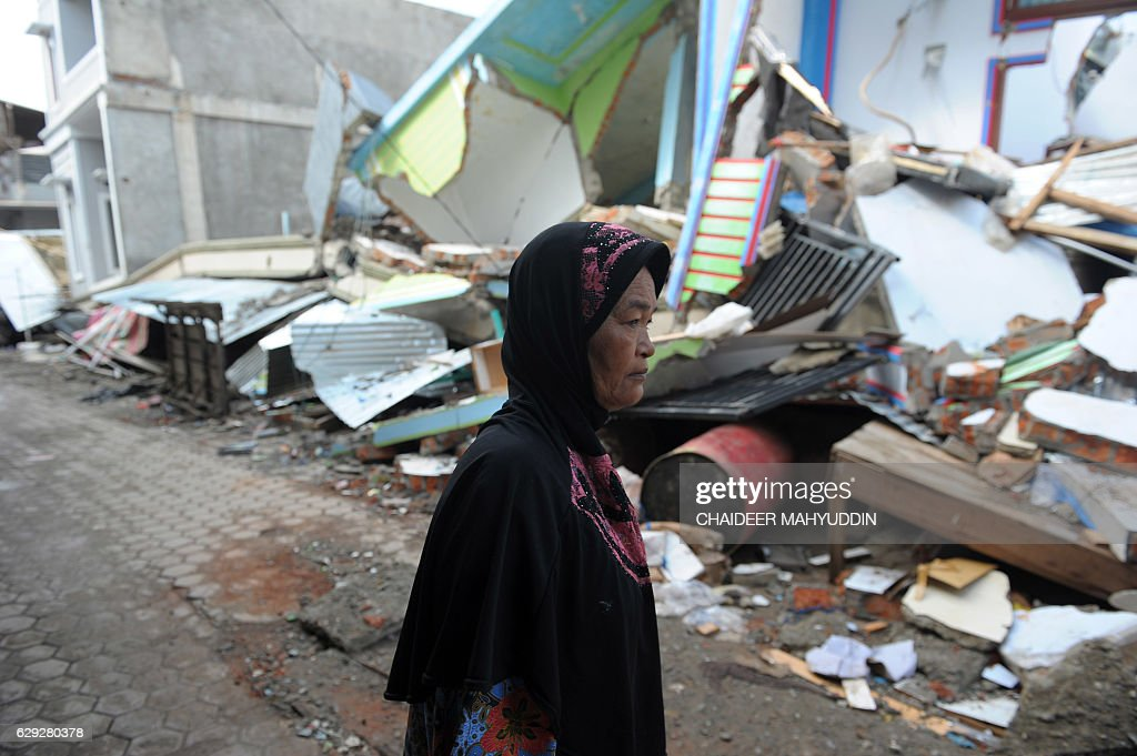 An Acehnese woman walks past damaged houses after 6.5 Magnitude earthquake hit in Pidie Jaya, Aceh province on December 12, 2016