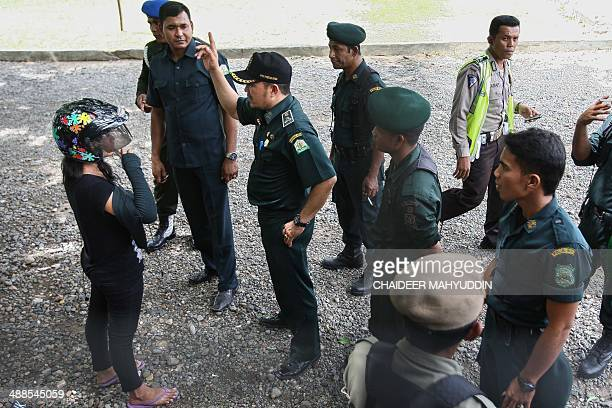 An Acehnese woman who was riding a motorcycle is arrested by sharia police for violating sharia law for wearing tight jeans and without hijab head...