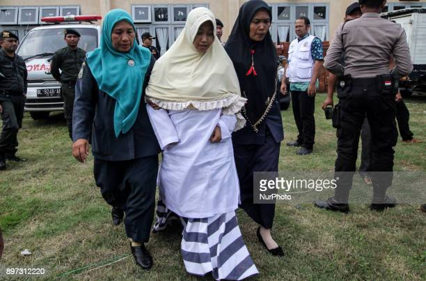 An Acehnese women is whipped in front of the public for violating sharia law at Islamic Center Mosque Lhokseumawe in Aceh Province Indonesia on...