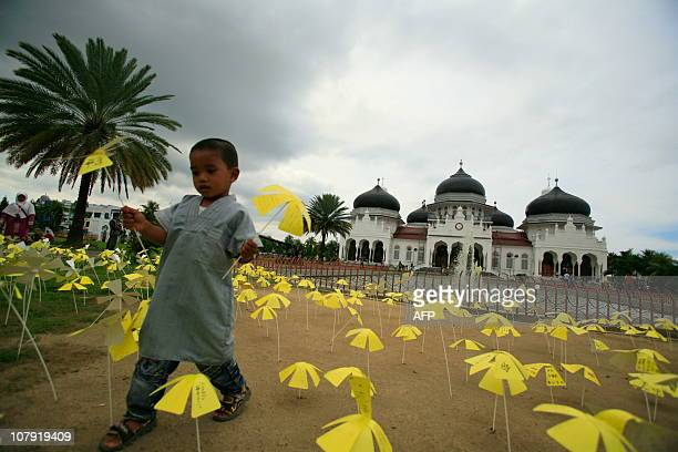 An Acehnese young boy holds paper flowers provided by Japanese people from Kobe as part of the 6th earthquake and tsunami anniversary in Banda Aceh...