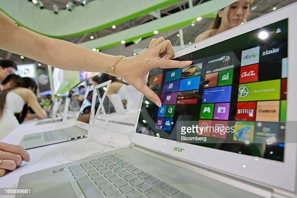 An Acer Inc employee demonstrates an Aspire 7 laptop at the company's booth at Computex Taipei 2013 in Taipei Taiwan on Tuesday June 4 2013 Computex...