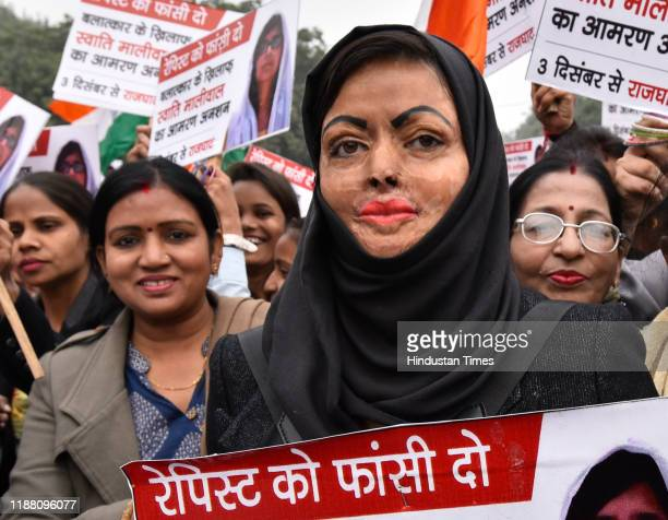 An acid attack survivor holds up a placard in support of Swati Maliwals hunger strike during a protest in solidarity with rape victims and to...