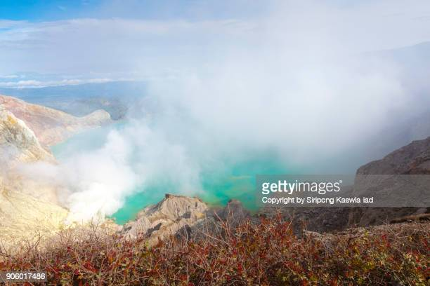 An acidic gas of sulphur floating over the turquoise lake inside the Kawah Ijen crater, Indonesia.