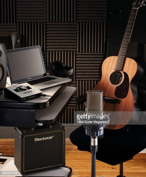 An acoustic guitar and audio hardware photographed for a feature on recording your own music including an Apple Macbook Universal Audio Apollo Twin...